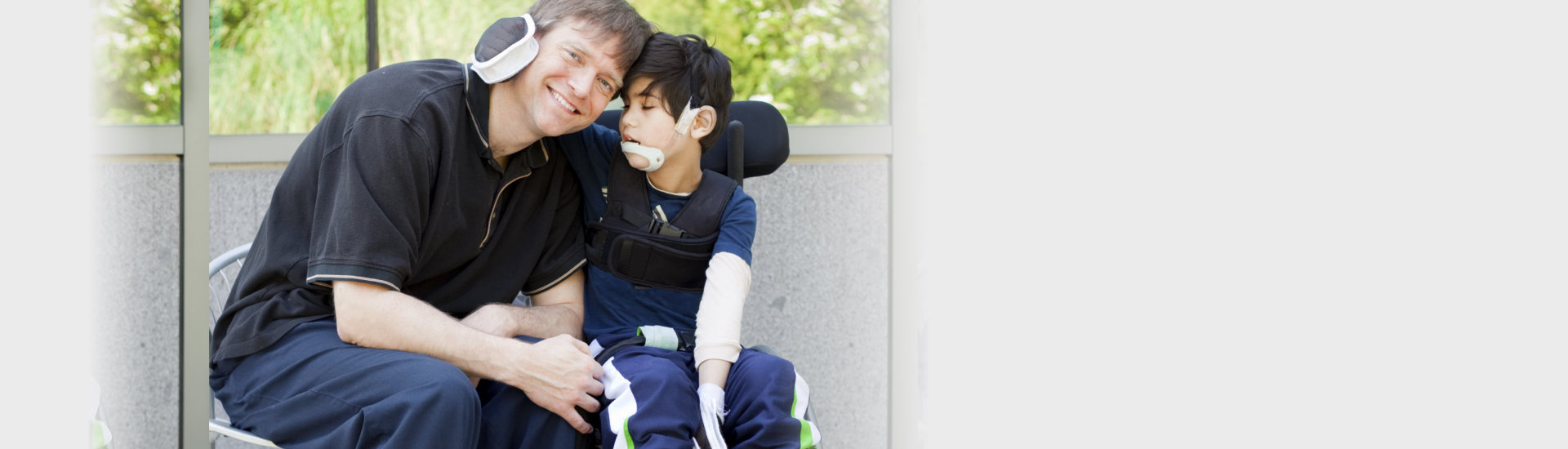 disabled boy hugging his father