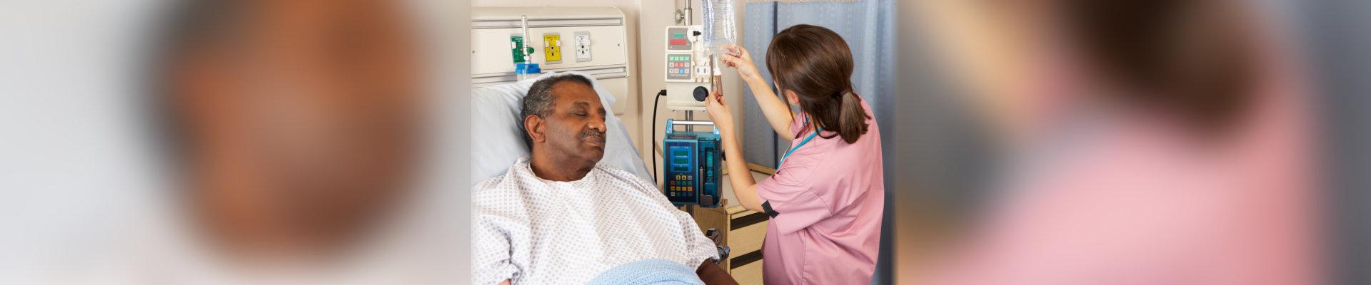 nurse checking on an old man's iv drip